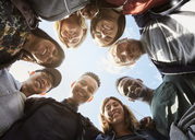 Low angle portrait of smiling friends huddling at university campus against sky - MASF01757