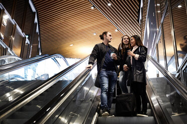 Low angle view of friends with luggage talking while moving down on escalator at underground station - MASF01769
