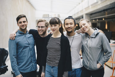 Group portrait of confident male and female computer programmers standing together in office - MASF01778