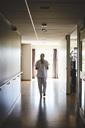 Full length rear view of female nurse walking in hospital corridor - MASF01784
