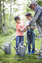 Grandfather with grandsons holding garden hose while filling watering cans in back yard - MASF01793