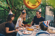 Happy family of four enjoying crayfish party in yard - MASF01802