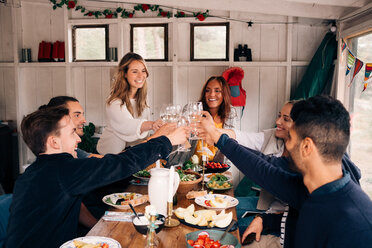 Happy men and women toasting wineglasses in cottage - MASF01811
