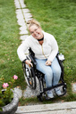 Full length portrait of smiling disabled woman sitting on wheelchair in backyard - MASF01829
