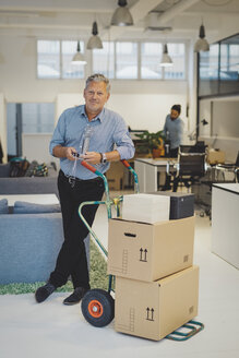 Full length portrait of confident mature businessman standing by luggage cart with stacked cardboard boxes in new office - MASF01847