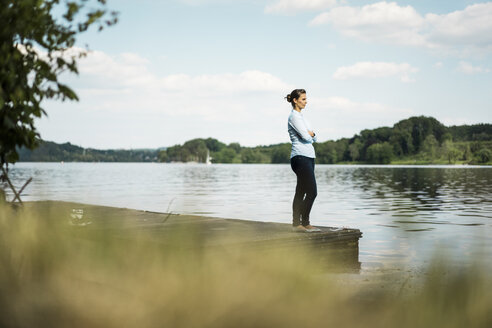 Woman standing on jetty at a lake - JOSF02166