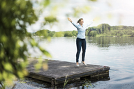 Woman doing a jumping jack on jetty at a lake - JOSF02172