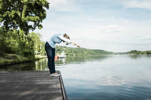 Woman on jetty wearing VR glasses pretending to dive into a lake - JOSF02175