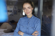 Portrait of smiling woman wearing denim shirt leaning against opened window - PNEF00580