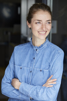 Portrait of smiling woman wearing denim shirt leaning against open window - PNEF00583