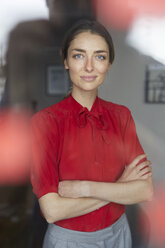 Portrait of smiling woman wearing red blouse standing behind windowpane - PNEF00586