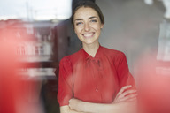 Portrait of laughing woman behind windowpane wearing red blouse - PNEF00589