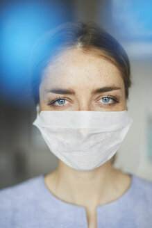 Portrait of woman wearing surgical mask - PNEF00595