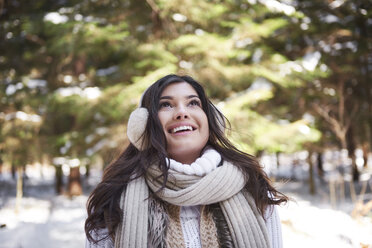 Portrait of happy young woman in winter forest - ABIF00283