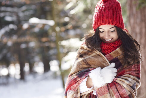 Smiling young woman wrapped in  blanket in winter forest - ABIF00286