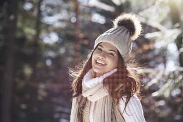 Portrait of laughing young woman wearing knitwear in winter forest - ABIF00289