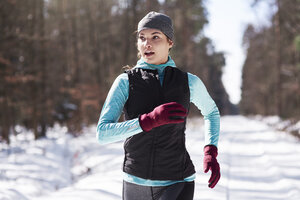 Portrait of young woman jogging in winter forest - ABIF00292