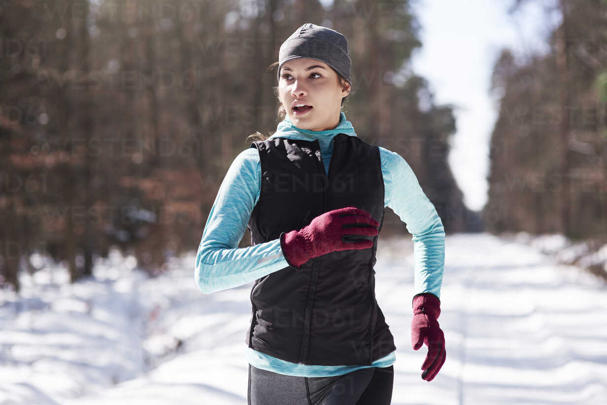 Portrait of young woman jogging in winter forest - ABIF00292 - gpointstudio/Westend61