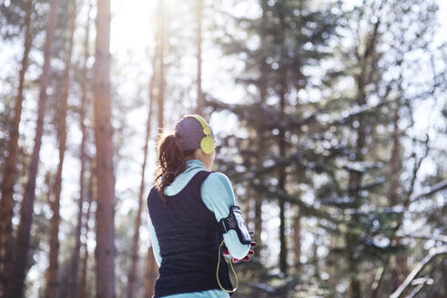 Back view of young jogger with headphones in forest having a break - ABIF00295