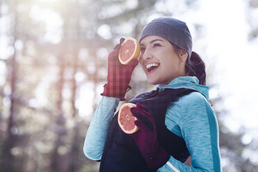 Portrait of laughing young woman wearing sportswear holding two halves of grapefruit - ABIF00298
