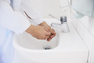 Cropped of male doctor washing hands in sink at hospital - MASF01862