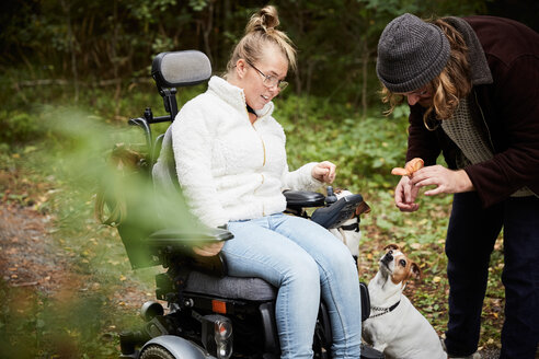 Disabled woman in wheelchair looking at caretaker holding mushroom in forest - MASF01871