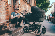 Father using smart phone while holding baby carriage on steps at building entrance - MASF01898