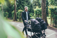 Full length of man pushing baby carriage on footpath - MASF01901