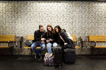 Full length of friends looking at smart phone while sitting against wall on subway station platform - MASF01925