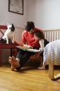 Father and daughter looking at book while sitting with dog at home - CAVF35391