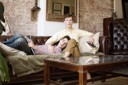 Portrait of gay couple relaxing on sofa - CAVF35460