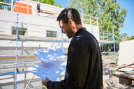 Businessman reading blueprints while standing at construction site on sunny day - MASF01932