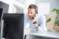Businessman talking on mobile phone while using computer at desk in office - MASF01935
