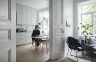 Businesswoman using laptop on table seen through doorway at home - MASF01944