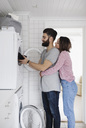 Woman embracing man while loading clothes in washing machine at home - MASF01956