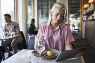 Young blond businesswoman using digital tablet while sitting at table in restaurant - MASF01959