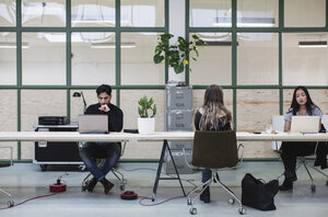 Two women and one man working at desk in creative office - MASF01971