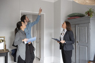 Woman and female realtor looking at man pointing up while standing in room - MASF01986
