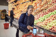 Woman holding apple by shopping cart against man standing at supermarket - MASF01995