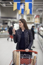 Woman talking on mobile phone through headphones while standing with shopping cart at supermarket - MASF01998