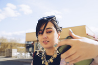 Young woman taking selfie with smart phone in city - MASF02001