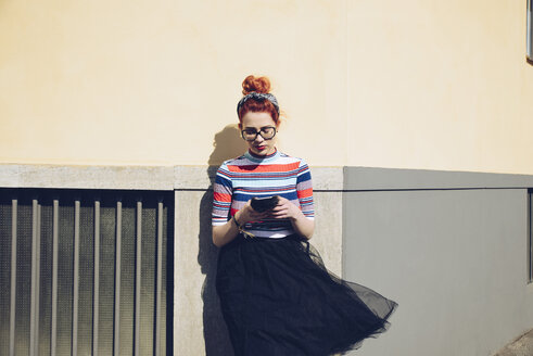 Young female hipster using mobile phone while standing against wall - MASF02004
