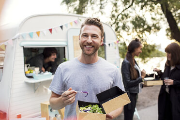 Smiling male customer holding disposable salad box against food truck with friends and owner in background - MASF02019