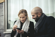 Smiling businesswoman looking at businesswoman using smart phone against window - MASF02025