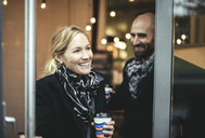 Smiling mid adult businesswoman and businessman leaving cafe - MASF02028