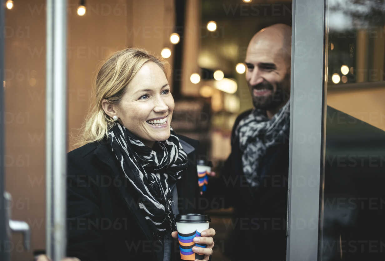 Smiling mid adult businesswoman and businessman leaving cafe - MASF02028 - Maskot ./Westend61