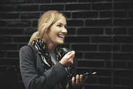 Smiling mid adult woman using hands-free device against brick wall - MASF02031
