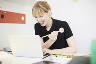 Smiling businesswoman eating lunch while using laptop in office - MASF02034