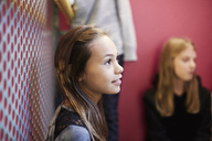 Thoughtful girl looking away with friends in background at middle school - MASF02040
