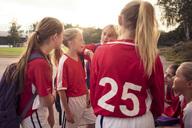 Soccer girls talking on footpath against sky - MASF02049